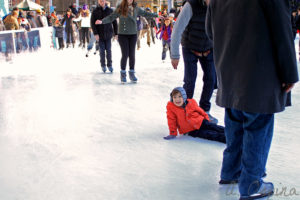 Kid smiling after falling on the ice at the Bryant Park ice skating rink