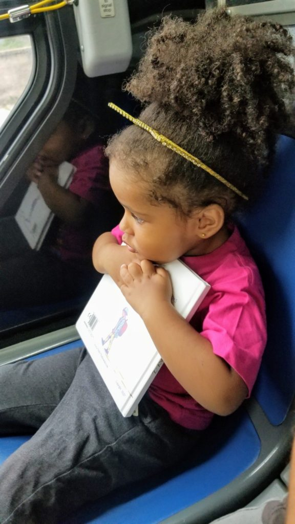 toddler hugging book MTA bus
